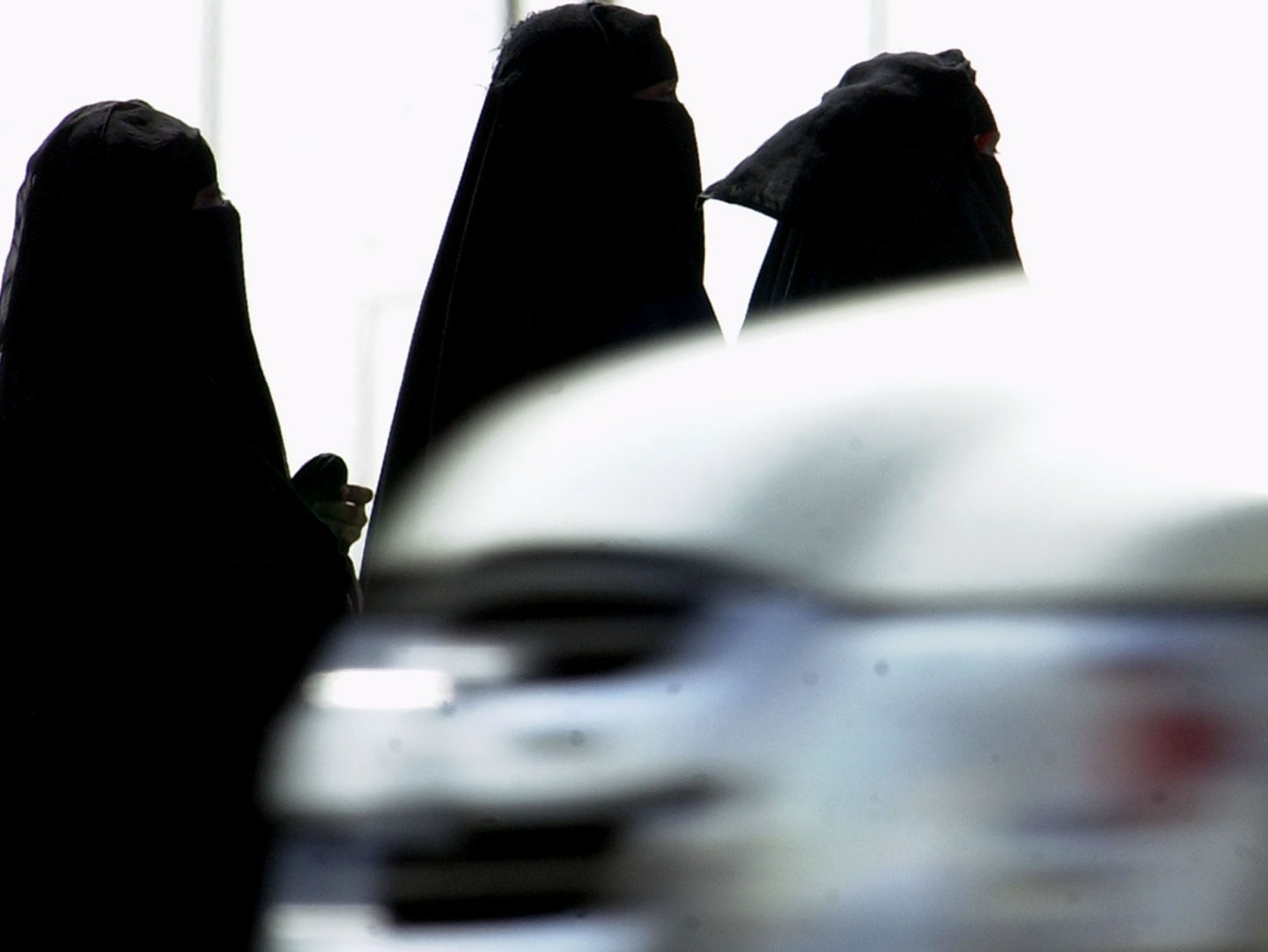 FILE - In this Wednesday, Nov. 15, 2006 file photo, Saudi women walk past cars in a Riyadh, Saudi Arabia, street. A Saudi lawyer and rights advocates say authorities will bring a Saudi activist to trial for defying the kingdom's female driving ban. (AP Photo/Hasan Jamali, File)